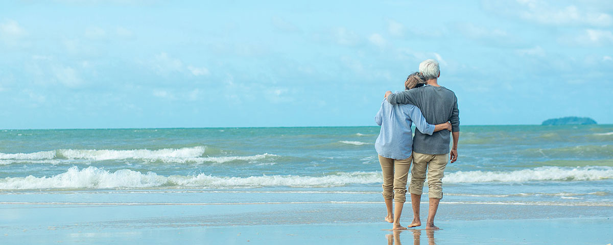 An elderly couple looking out over the ocean, hugging each other.