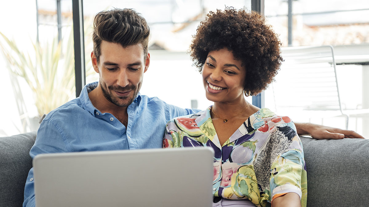 A Caucasian male and African-American woman looking at a laptop together, smiling.
