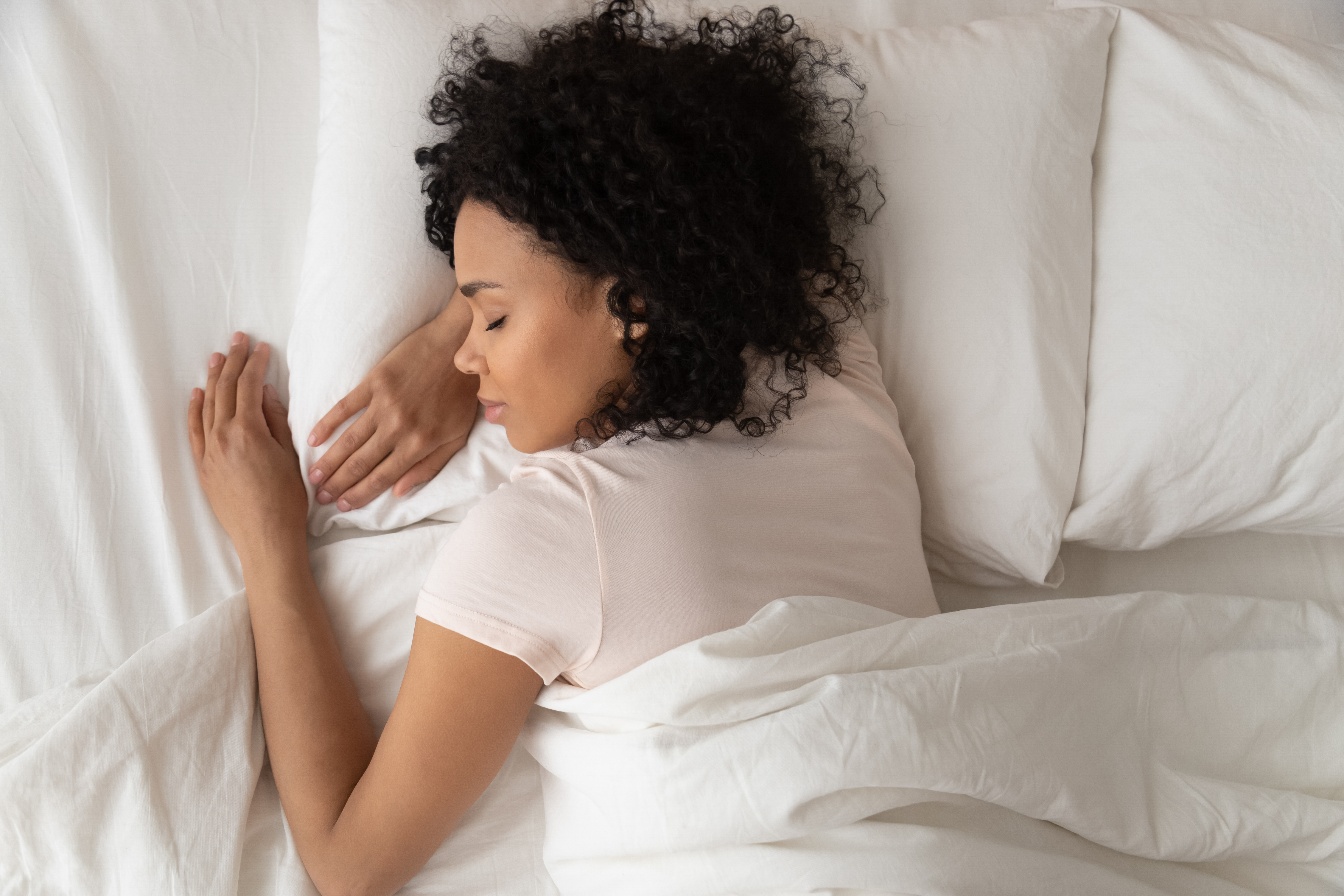 African-American woman sleeping on her stomach on a bed with fresh sheets